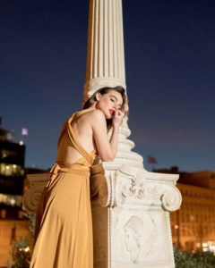 Our model in the Calypso Polymorphic Maxi Dress, in the Yellow Mustard shade from the side