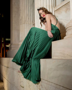 Our model in the Frances Stevens Grecian Pleated Dress, in the Emerald Green shade from the side